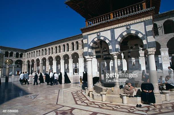 Syria South Damascus The Umayyad Mosque The ablutions fountain with pilgrims sitting around the hexagonal base and crossing the marble courtyard...