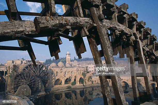 Syria Wooden waterwheels on the Orontes river framing the AlNuri Mosque