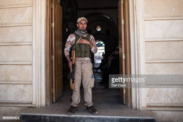 Syriac Christian militiaman guards an entrance to Saint John's Church during an easter ceremony in the nearly deserted predominantly Christian Iraqi...