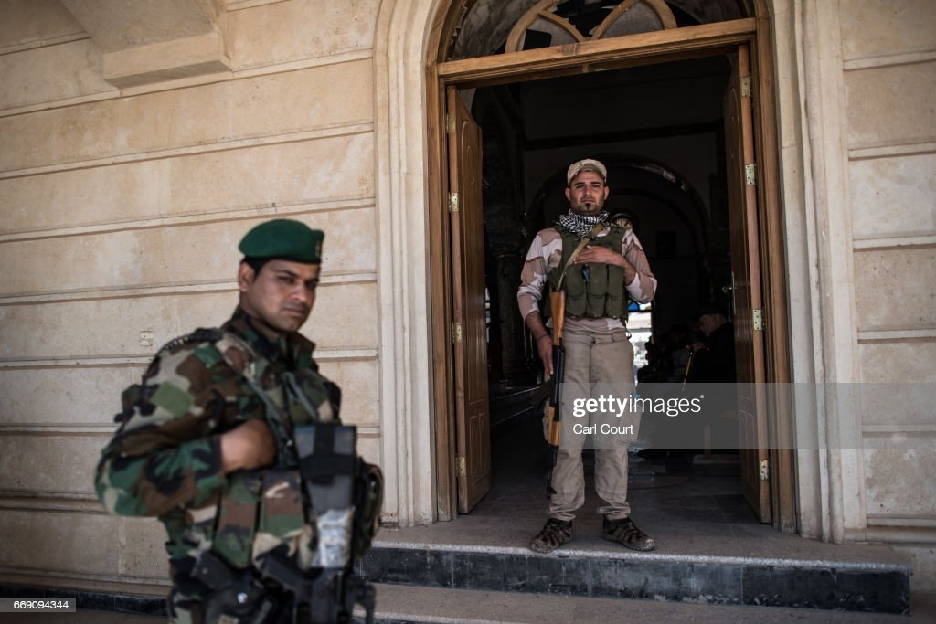 Syriac Christian militiamen guard Saint John's Church (Mar Yohanna) during an easter ceremony in the nearly deserted predominantly Christian Iraqi town of Qaraqosh on April 16, 2017 near Mosul, Iraq. Qaraqosh was retaken by Iraqi forces in 2016 during the offensive to capture the nearby city of Mosul from Islamic State but it remains almost completely deserted.