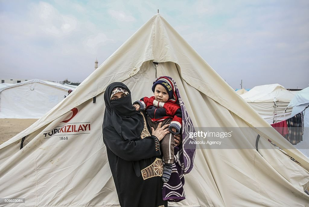A Syrian 1 year old baby Abdulgaffur Sali, who fled bombing in Aleppo, is seen on his mother Fatma Hanyani's arms at a tent city close to the Bab al-Salam border crossing on Turkish-Syrian border near Azaz town of Aleppo, Syria on February 11, 2016. Russian airstrikes have recently forced some 40,000 people to flee their homes in Syrias northern city of Aleppo.