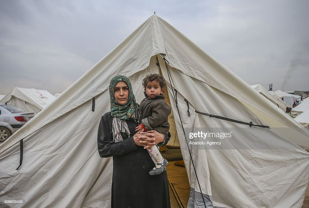 A Syrian 1 year old baby Islam Sabhi, who fled bombing in Aleppo, is seen on her mother Vetfa Sabhi's arms at a tent city close to the Bab al-Salam border crossing on Turkish-Syrian border near Azaz town of Aleppo, Syria on February 11, 2016. Russian airstrikes have recently forced some 40,000 people to flee their homes in Syrias northern city of Aleppo.
