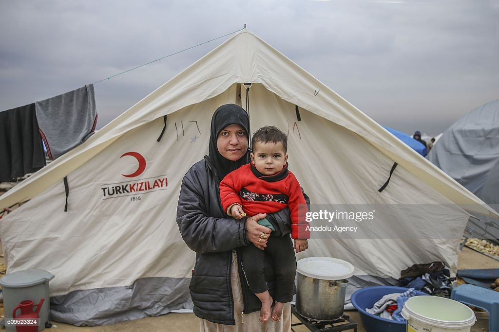 A Syrian 2 year old baby Khaleed Heffar, who fled bombing in Aleppo, is seen on his mother Imen Hassan's arms at a tent city close to the Bab al-Salam border crossing on Turkish-Syrian border near Azaz town of Aleppo, Syria on February 11, 2016. Russian airstrikes have recently forced some 40,000 people to flee their homes in Syrias northern city of Aleppo.
