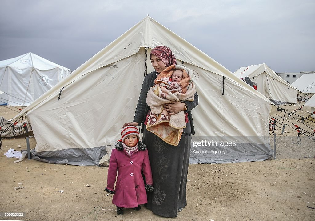 A Syrian 2 year old baby Zehra and Eye Halip, who fled bombing in Aleppo, are seen with their mother Belkiz Halip at a tent city close to the Bab al-Salam border crossing on Turkish-Syrian border near Azaz town of Aleppo, Syria on February 11, 2016. Russian airstrikes have recently forced some 40,000 people to flee their homes in Syrias northern city of Aleppo.