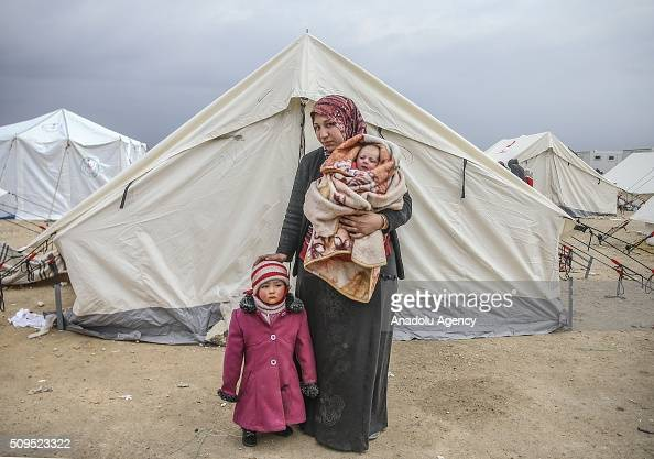 ALEPPO, SYRIA - FEBRUARY 11: A Syrian 2 year old baby Zehra and Eye Halip, who fled bombing in Aleppo, are seen with their mother Belkiz Halip at a tent city close to the Bab al-Salam border crossing on Turkish-Syrian border near Azaz town of Aleppo, Syria on February 11, 2016. Russian airstrikes have recently forced some 40,000 people to flee their homes in Syrias northern city of Aleppo. (Photo by Fatih Aktas/Anadolu Agency/Getty Images)