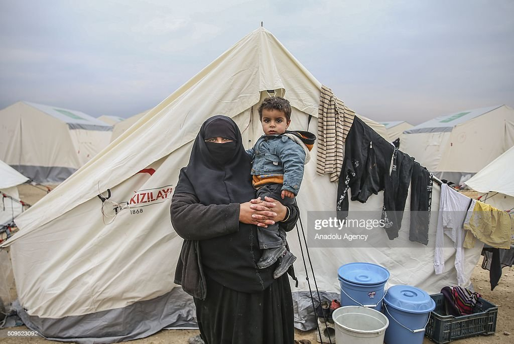 A Syrian 2 year old Omar Muhammad, who fled bombing in Aleppo, is seen on his mother Zarifa Muhammad's arms at a tent city close to the Bab al-Salam border crossing on Turkish-Syrian border near Azaz town of Aleppo, Syria on February 11, 2016. Russian airstrikes have recently forced some 40,000 people to flee their homes in Syrias northern city of Aleppo.