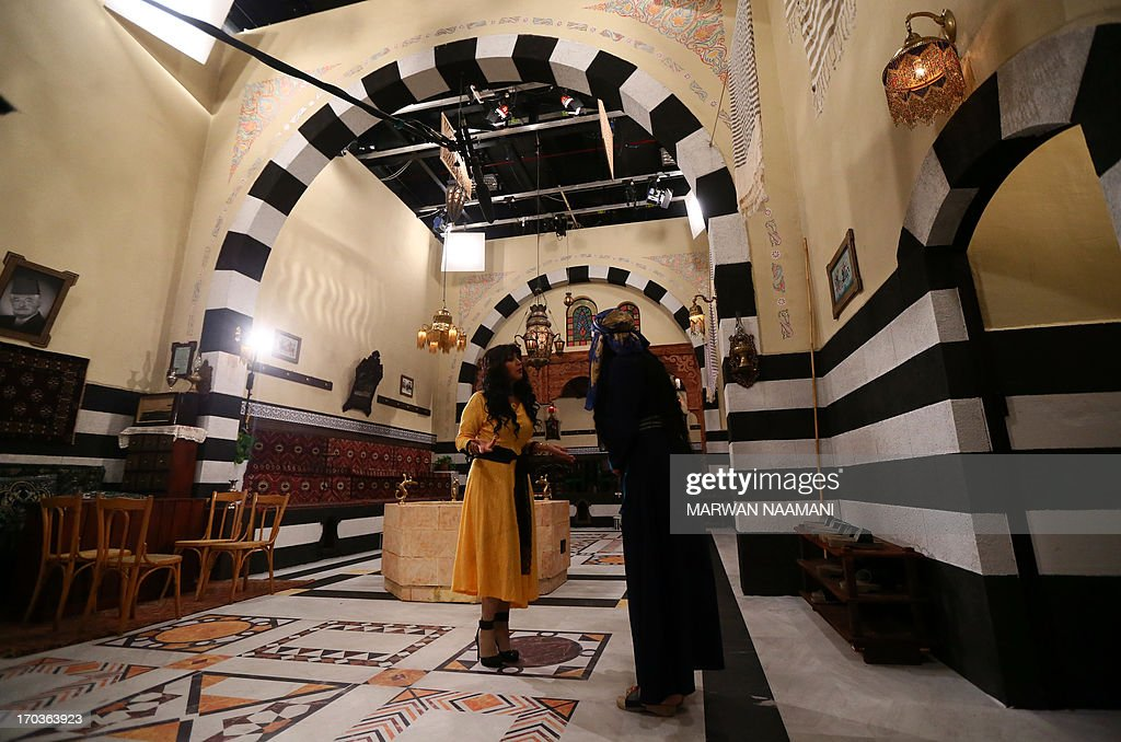 Syrian actresses Waha al-Rahib (L) and Jinan Bakr perform during the shooting of a sequence of TV series 'Hamam Shami' or 'Syrian Bath' in a studio in Abu Dhabi, on June 3, 2013. A traditional Damascene bath comes to life in the Emirates as a team of Syrian actors bustle around in wooden clogs on a film set built far away from war-torn Syria. The scene is from 'Hammam Shami' a Syrian soap to be broadcast during the Muslim holy month of Ramadan in July, and for which the settings have been built for the first time outside Syria.