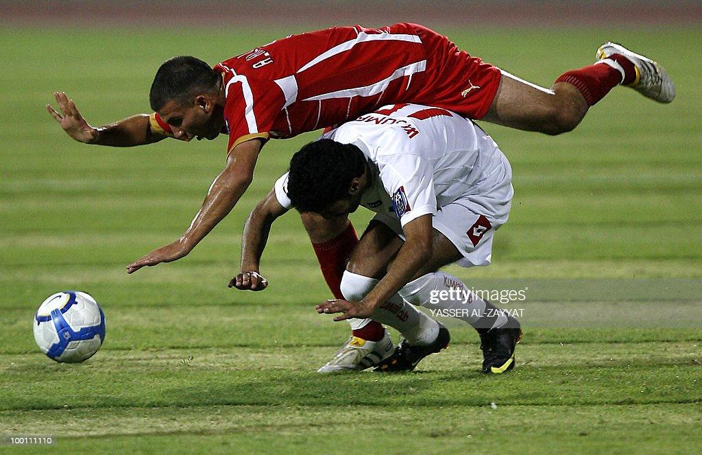 Syrian Al-Ittihad's Ahmed Kalasi (top) trips over Kuwait SC's Walid Ali during their AFC Cup round of 16 football match in Kuwait City on May 12, 2010.