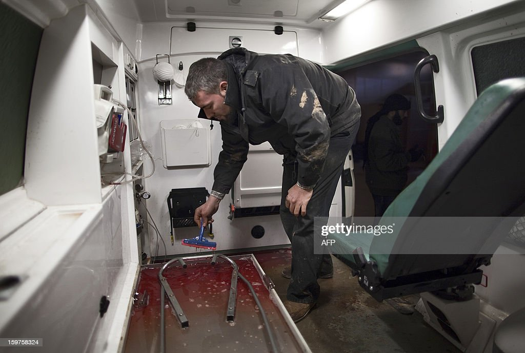 Syrian ambulance driver Abu Mohammed cleans blood after ferrying the wounded in the war-torn northern city of Aleppo on January 12, 2013. The accident and emergency centre in Aleppo uses an abandoned supermarket to conceal a fleet of 16 ambulances, just 10 of which are in working order and are driven by 22 staff members. AFP PHOTO/JM LOPEZ