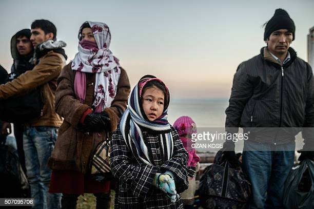 TOPSHOT Syrian and Afghan migrants and refugees wait after being caught by Turkish gendarme on January 27 2016 at Canakkale's Kucukkuyu district The...
