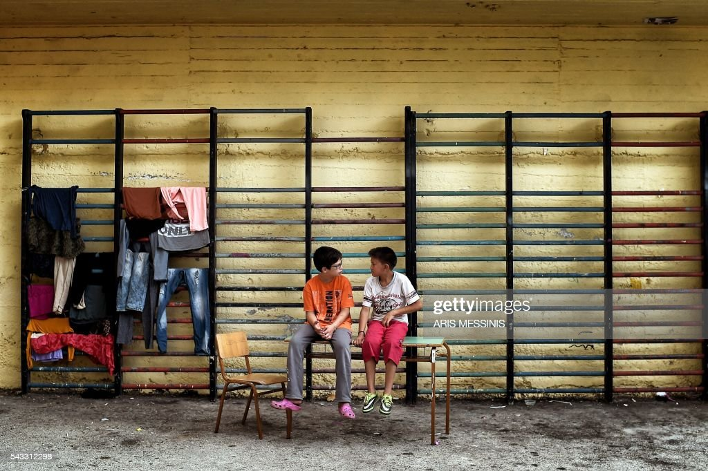 A Syrian and an Afghan boy chat as they sit at the yard of an abandoned school used by volunteers for hosting families of refugeees from Syria and Afghanistan in Athens on June 27, 2016. / AFP / ARIS