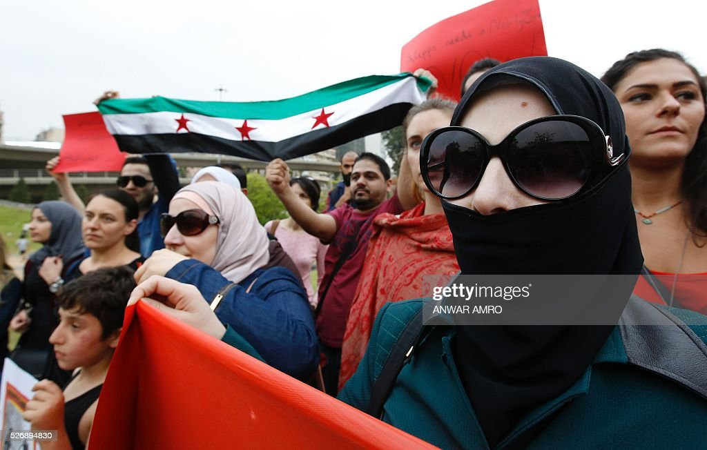 Syrian and Lebanese protesters hold banners and the Syrian flag as they take part in a demonstration in front of United Nations offices in Beirut in solidarity with the civilians of the northern Syrian city of Aleppo and against the regime of the Syrian president, on May 1, 2016. / AFP / Anwar AMRO