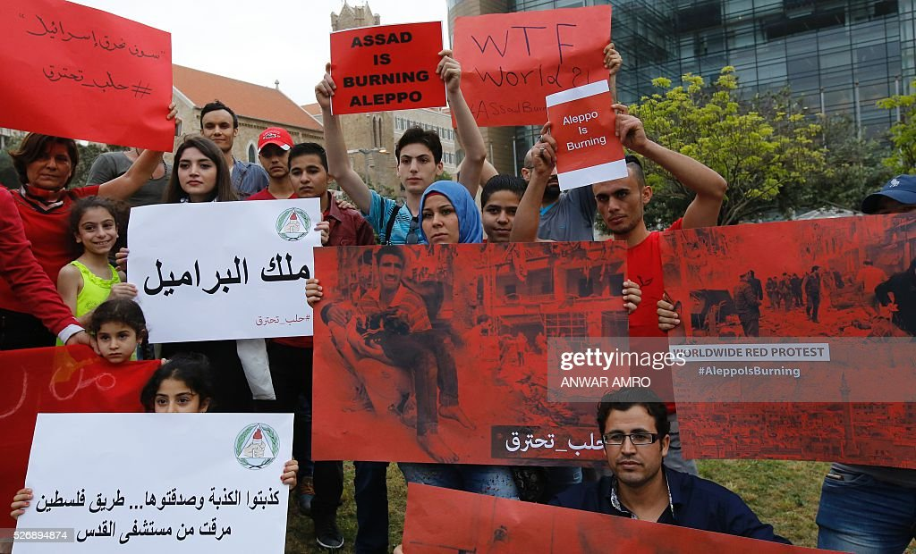Syrian and Lebanese protesters hold banners as they take part in a demonstration in front of United Nations offices in Beirut in solidarity with the civilians of the northern Syrian city of Aleppo and against the regime of the Syrian president, on May 1, 2016. / AFP / Anwar AMRO