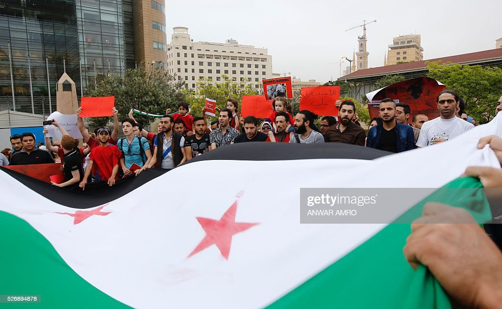 Syrian and Lebanese protesters wave the Syrian flag as they take part in a demonstration in front of United Nations offices in Beirut in solidarity with the civilians of the northern Syrian city of Aleppo and against the regime of the Syrian president, on May 1, 2016. / AFP / Anwar AMRO