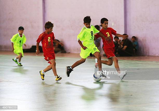 Syrian and Palestinian refugee children wear new sports gear they received for their soccer match at the AlBaqaa Palestinian refugee camp June 17...