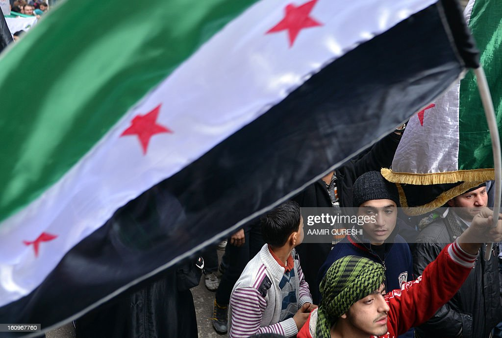 Syrian anti-regime protesters wave a pre-Baath Syrian flag, now used by the Free Syrian Army, during a demonstration after the weekly Friday prayers in the Bustan al-Qasr district of the northern city of Aleppo on February 8, 2013. Syrian forces shelled rebel belts, the Syrian Observatory for Human Rights said, as an army offensive raged into a third straight day. AFP PHOTO/AAMIR QURESHI