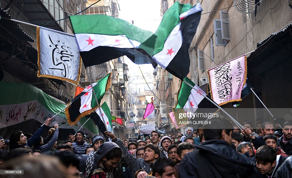 Syrian anti-regime protesters wave pre-Baath Syrian flags, now used by the Free Syrian Army, during a demonstration after the weekly Friday prayers in the Bustan al-Qasr district of the northern city of Aleppo on February 8, 2013. Syrian forces shelled rebel belts, the Syrian Observatory for Human Rights said, as an army offensive raged into a third straight day.