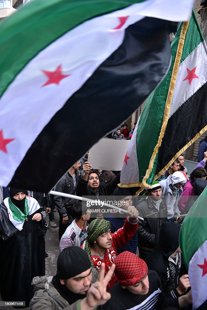 Syrian anti-regime protesters wave pre-Baath Syrian flags, now used by the Free Syrian Army, during a demonstration after the weekly Friday prayers in the Bustan al-Qasr district of the northern city of Aleppo on February 8, 2013. Syrian forces shelled rebel belts, the Syrian Observatory for Human Rights said, as an army offensive raged into a third straight day. AFP PHOTO/AAMIR QURESHI