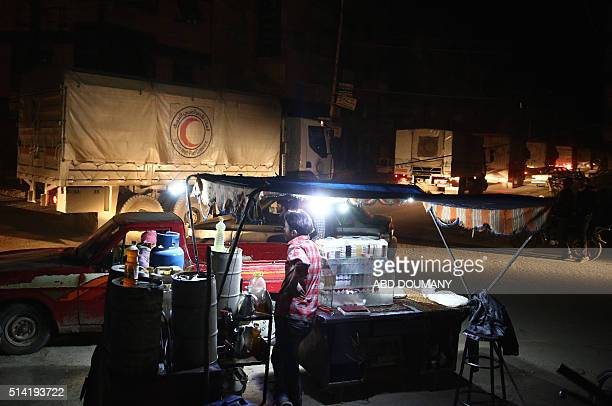 A Syrian Arab Red Crescent convoy carrying humanitarian aid drives past a Syrian man selling goods in a street in Hammuriya in the eastern Ghouta...