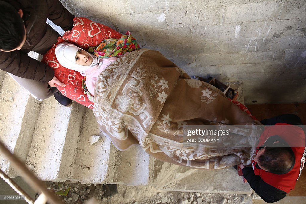 TOPSHOT Syrian Arab Red Crescent volunteers carry an injured Syrian child as they leave her home to attend an event organised for children by the...