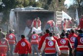 Syrian Arab Red Crescent workers offload aid from a lorry as Syrians evacuated from rebelcontrolled districts that were besieged by the army arrive...