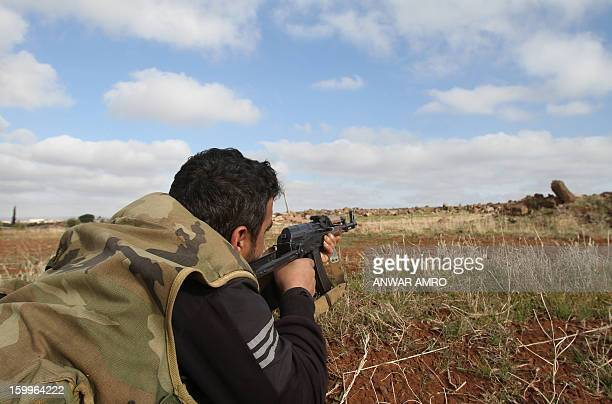A Syrian army fighter points his rifle towards the rebelheld province of Daraa as he takes position on the green Line in Mjeimer in the mainlyDruze...