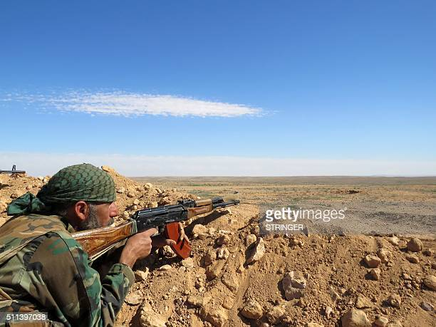 A Syrian army soldier takes aim from a position on the outskirts of Syria's Raqa region on February 19 2016 / AFP / STRINGER
