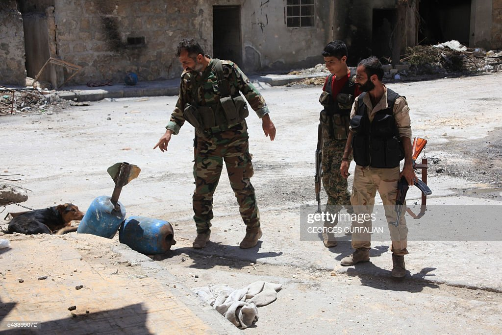 Syrian army soldiers check unexploded homemade rockets during a patrol in government-controlled Aleppo's al-Khalidiya area where the army progressed towards the industrial zone of al-Layramoun and Bani Zeid on June 28, 2016. Aleppo was once the country's commercial hub but now lies divided between government forces in the west and rebels in the east. OURFALIAN