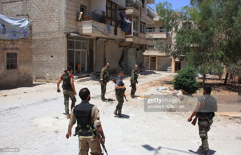 Syrian army soldiers patrol a street in government-controlled Aleppo's al-Khalidiya area where the army progressed towards the industrial zone of al-Layramoun and Bani Zeid on June 28, 2016. Aleppo was once the country's commercial hub but now lies divided between government forces in the west and rebels in the east. OURFALIAN