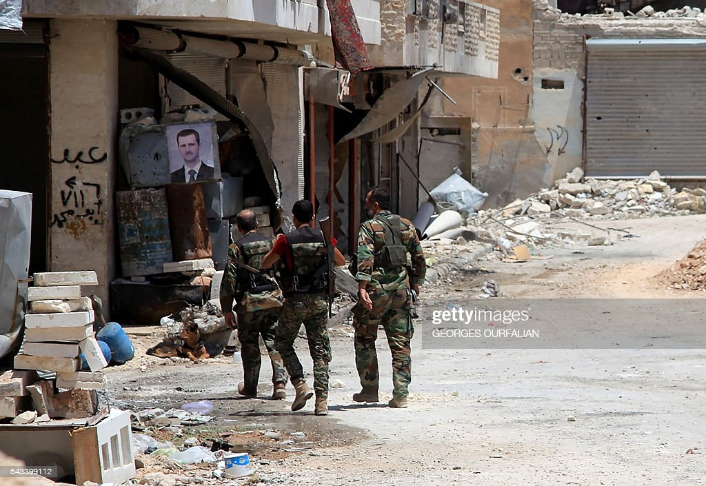 Syrian army soldiers patrol in government-controlled Aleppo's al-Khalidiya area where the army progressed towards the industrial zone of al-Layramoun and Bani Zeid on June 28, 2016. Aleppo was once the country's commercial hub but now lies divided between government forces in the west and rebels in the east. OURFALIAN