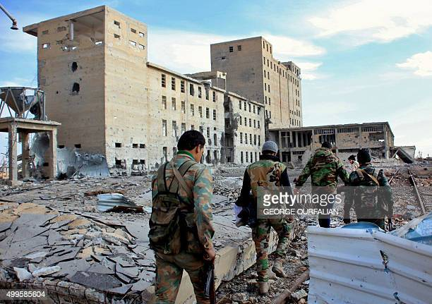 Syrian army soldiers patrol near a building previously used for storing seeds in the countryside of Deir Hafer a former bastion of Islamic State...