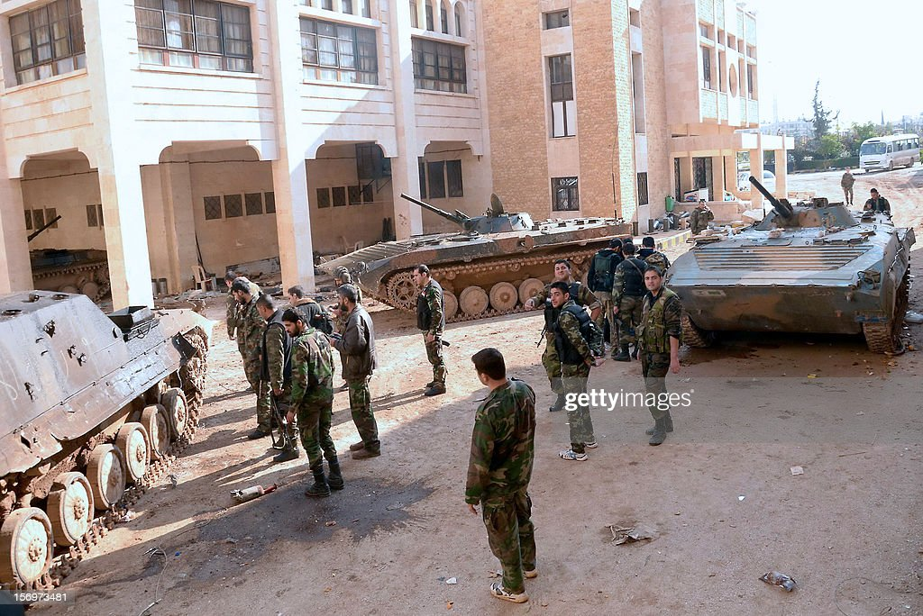 Syrian army soldiers stand by their armoured vehicles in the al-Layramun district of the northern city of Aleppo, which is under government troops control, on November 26, 2012. Syrian rebels aiming to encircle Aleppo virtually cut off roads to the city from neighbouring Raqqa province as the army targeted rebel strongholds around Damascus.
