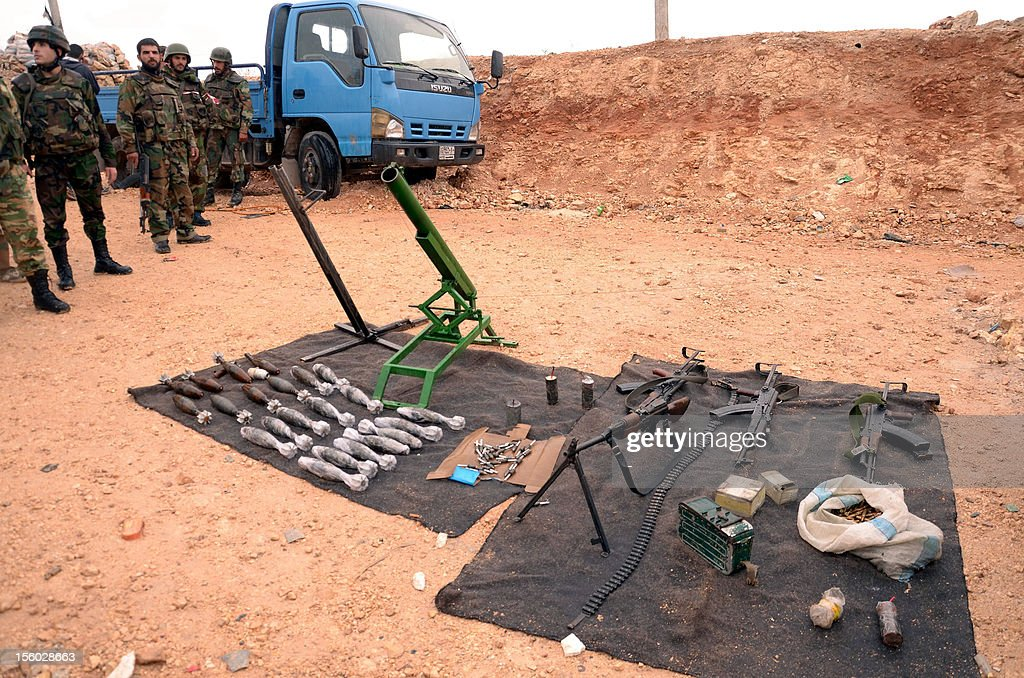 Syrian army soldiers stand next to weapons that were allegedly confiscated from opposition fighters in the Sheik Said neighbourhood of Syria's northern city of Aleppo on November 11, 2012 after they retook the area. The army retook a stretch of the Damascus-Aleppo highway in Idlib used for transporting reinforcements, but has failed to retake the strategic northwestern town of Maaret al-Numan.