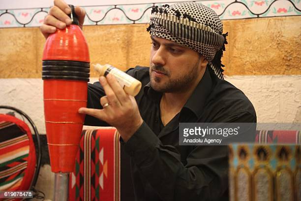 Syrian artist Akram Abu alFaiz paints rocket capsules empty shell casings and missiles which he collects for 5 years during Syrian Civil war at his...