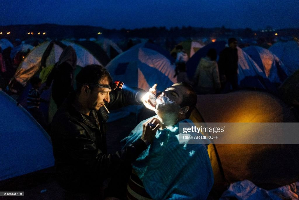 Syrian barber shaves the beard of a customer in a migrant and refugee makeshift camp installed close to Greek-Macedonian border near the Greek village of Idomeni, on March 5, 2016, where thousands of refugees and migrants wait to cross the border into Macedonia. Some 13,000 refugees are crammed in unhygienic conditions on Greece's border with Macedonia, officials said on March 5, with all eyes on a key EU-Turkey summit on March 7 that is seen as the only viable solution to the crisis. The huge influx of refugees and migrants has caused major tensions and divisions within the European Union, but EU President Donald Tusk on March 4 struck an upbeat note about the summit in Brussels. / AFP / DIMITAR