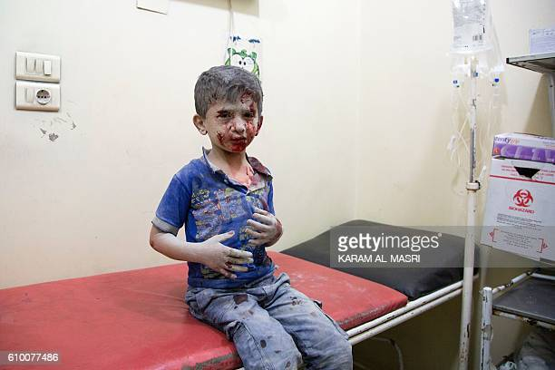 A Syrian boy awaits treatment at a makeshift hospital following air strikes on rebelheld eastern areas of Aleppo on September 24 2016 Heavy Syrian...