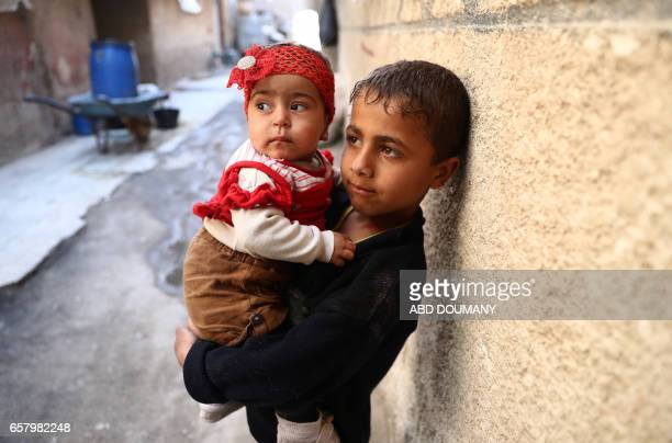 Syrian boy carries a child in the rebelcontrolled town of Kafr Batna in the eastern Ghouta region on the outskirts of the capital Damascus on March...