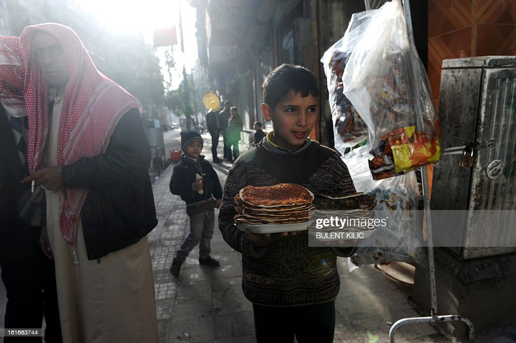 A Syrian boy carries food back to his family in the northern city of Aleppo on February 14, 2013. Syrian Foreign Minister Walid al-Muallem and opposition National Coalition chief Ahmed Moaz al-Khatib will make separate visits to Moscow for talks in the coming weeks, a top Russian diplomat said.