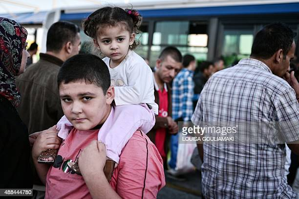 A Syrian boy carries his sister after disembarking at the port of Piraeus from the Greek island of Kos on September 16 2015 Over half a million...