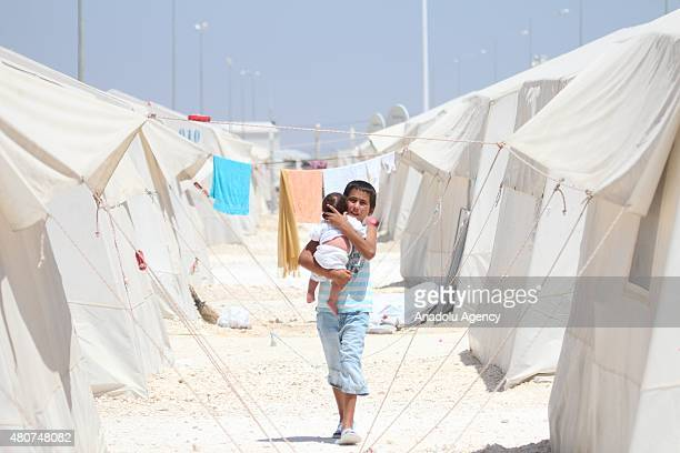Syrian boy carrying a baby walk past the tents at a refugee camp in Suruc district of Sanliurfa on July 14 as the Syrian Kurds who fled the clashes...