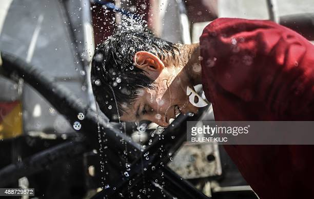 A Syrian boy cools off with water near the highway on September 17 on his way to the border between Turkey and Greece Around 1000 refugees remained...