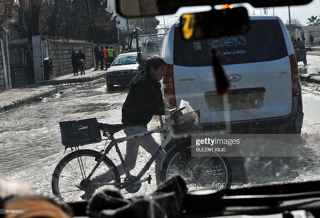 A Syrian boy crosses the street with his bicycle in the northern city of Aleppo on February 14, 2013. Syrian Foreign Minister Walid al-Muallem and opposition National Coalition chief Ahmed Moaz al-Khatib will make separate visits to Moscow for talks in the coming weeks, a top Russian diplomat said.