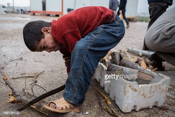 A Syrian boy cuts wood at a refugee camp near the northern city of Azaz on the SyriaTurkey border home to more than 7000 people mostly from the...