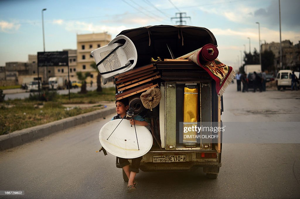A Syrian boy holds a satellite antenna as he travels on the back of a truck in the northern Syrian city of Aleppo on April 15, 2013. In all, some 1.3 million people have so far fled Syria to neighbouring countries since the beginning of the conflict, which has cost well over 70,000 lives. AFP PHOTO / DIMITAR DILKOFF