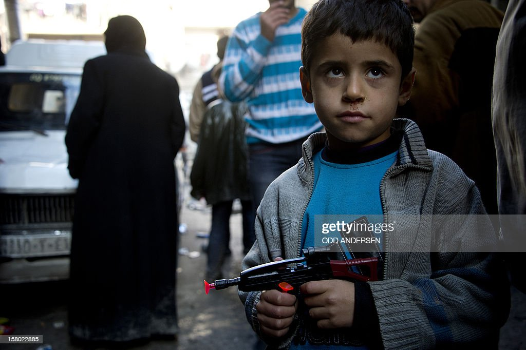 A Syrian boy holds a toy gun as he waits in the queue to buy bread outside a bakery in the al-Fardos neighbourhood of the northern Syrian city of Aleppo on December 9, 2012. The cost of basic commodities such as bread and fuel are rising in the city as Syrians have been struggling to continue their daily lives without water or electricity for one week now.