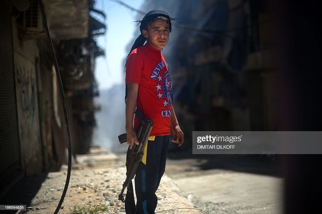 A Syrian boy holds an AK-47 assault rifle in the majority-Kurdish Sheikh Maqsud district of the northern Syrian city of Aleppo on April 14, 2013. In northern Syria, the Kurdish population has largely observed a careful compromise with regime and rebel forces, fighting alongside neither, in return for security and semi-autonomy over majority Kurdish areas, but there have been reports in recent weeks of Kurdish fighters joining the battle with Syrian rebels in certain areas, including in Sheikh Maqsud. AFP PHOTO / DIMITAR DILKOFF