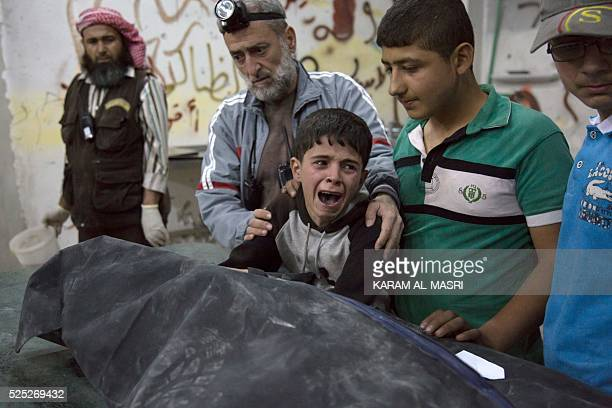Syrian boy is comforted as he cries next to the body of a relative who died in a reported airstrike on April 27 2016 in the rebelheld neighbourhood...