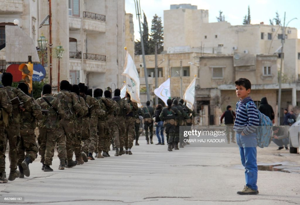 Syrian boy looks at rebel fighters from the Jaish al-Fatah (or Army of Conquest) brigades, which include other rebel factions, marching during a parade in the northwestern city of Idlib on March 13, 2017. / AFP PHOTO / Omar haj kadour