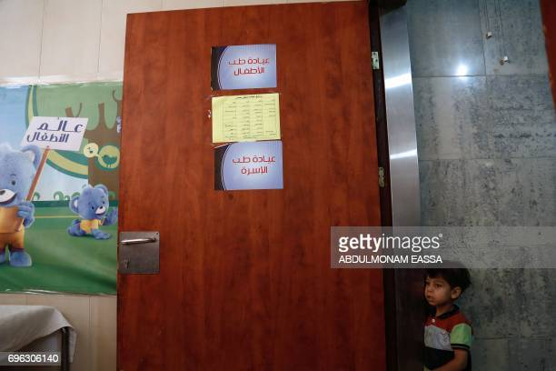 A Syrian boy looks on at a maternity clinic in the rebelheld town of Douma on the outskirts of the capital Damascus as a part of an awareness...