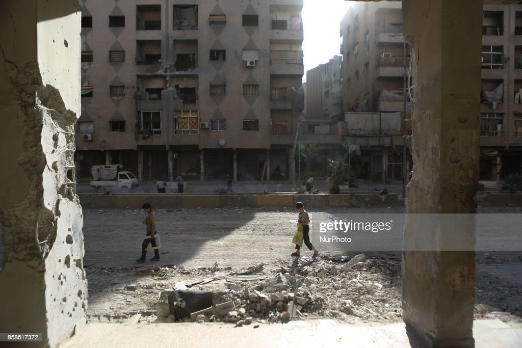 A Syrian boy looks towards the rubble of a building in the rebel. held town of Douma, on the eastern outskirts of Damascus, on October 6, 2017 following reported air strikes by Syrian government forces.